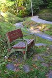 Bench by a Mountain Stream. Resting place by a peaceful mountain stream Royalty Free Stock Images