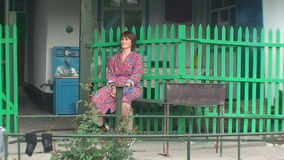 On a bench near the fence sitting woman stock video