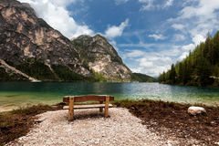 Bench near mountain lake Stock Images