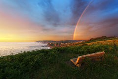 Bench near Sopelana coast with rainbow. And stormy weather stock image