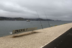 Bench near Tagus river and two rods. Lisbon, Portugal Royalty Free Stock Photos