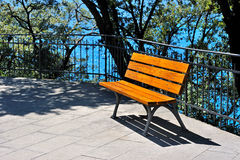 Bench near the water in the park on a sunny day Stock Photos