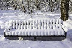 Bench nel parco dopo le precipitazioni nevose pesanti Royalty Illustrazione gratis