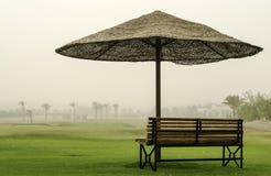 Bench no deserto sob um guarda-chuva do sol Foto de Stock Royalty Free