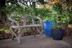 Bench no parque com os potenciômetros de flor coloridos Fotografia de Stock Royalty Free
