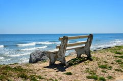 Bench on ocean shore Royalty Free Stock Image