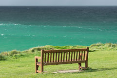 The bench on the ocean. A wooden bench on a green lawn by the ocean Stock Photos