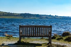 A bench onlooking Siblyback Lake in Cornwall, UK. An empty bench with an onlooking view of Siblyback Lake in Cornwall, UK Royalty Free Stock Photo