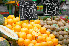 Bench of oranges and kiwi in a spanish market with a price list Stock Images