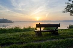 Bench over lake at sunrise Stock Photography
