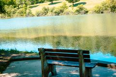 Bench over looking a pond on a sunny summer day royalty free stock photos