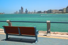 Bench overlooking Abu Dhabi buildings before sea Royalty Free Stock Image