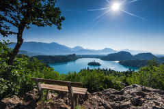 Bench overlooking Bled lake panoramic vista in full summer sun Royalty Free Stock Photo