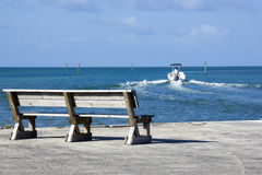Bench overlooking boat leaving the marina. Colorful seascapes in the Florida Keys Stock Image