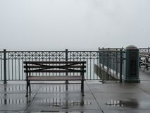 Bench overlooking foggy bay on rainy day royalty free stock image