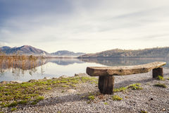 The bench overlooking the lake. A beautiful lake landscape with a wooden bench in the foreground stock photos