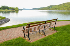 Bench Overlooking Lake. Park bench next to brick path overlooking Lake Otesaga, Cooperstown, New York. Known as Glimmerglass in the Leatherstocking Tales of stock photos