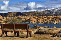 Bench overlooking a Lake with a Snow Capped Mountain Stock Images