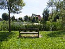 Bench overlooking a picturesque village pond. Bench on a grassy hill overlooking a picturesque tranquil village pond or lake with reeds in a lush landscape Royalty Free Stock Photo