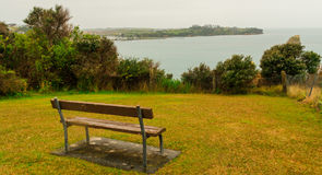 Bench overlooking the sea with a rock Stock Photos