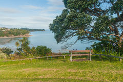 A bench overlooking the sea, Whangaparaoa, Auckland, New Zealand Stock Image