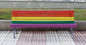 Bench painted in rainbow colors. In the street royalty free stock images