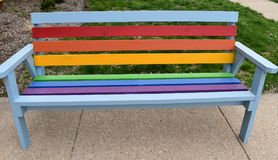 Bench painted in rainbow colors. Wooden outdoor bench painted in pride colors in an urban setting on a spring day stock photography