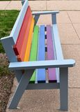 Bench painted in rainbow colors. Wooden outdoor bench painted in pride colors in an urban setting on a spring day stock images