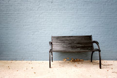 Bench with painted wall. Old black bench with painted brick wall Stock Photo
