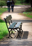 Bench  in park. Empty wooden bench near the park path, couple walking away Royalty Free Stock Image