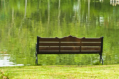 Bench In The Park. Bench over green lake in the park Royalty Free Stock Images