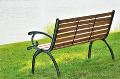 Bench in park. Empty bench on green grass in park by river Stock Image