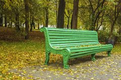 A bench in the park in autumn. And around yellow leaves Stock Photography
