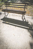 Bench in a park. Autumn leaves. Backlight Royalty Free Stock Photos