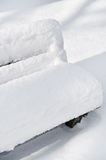 Bench in a park covered completely by snow Stock Images