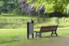 Bench in a park. Bench with dust bin next to it in a park Royalty Free Stock Photo