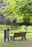 Bench in a park. Bench with dust bin next to it in a park Royalty Free Stock Image