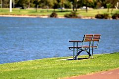 Bench in park near water Royalty Free Stock Image