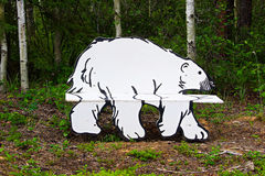 A bench in a park that is the shape of a polar bear Royalty Free Stock Photo