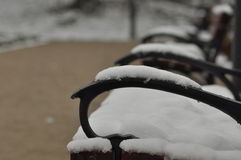 Bench in the park. Snow lying on the seat. Winter. Walk around the outside Royalty Free Stock Photo