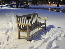 Bench in park on a snowy evening Stock Photography