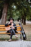 Bench in park. Vertical photo young man speaking phone and hold classic guitar in hads on the park royalty free stock photo