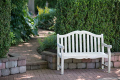 Bench and Path Blur. A whitewashed bench sits near a brick walkway that gradually disappears in soft focus Stock Images