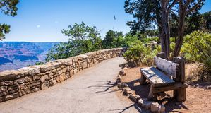 Bench on the path at the Grand Canyon Village. Picturesque overview of the Grand Canyon, Arizona Stock Image