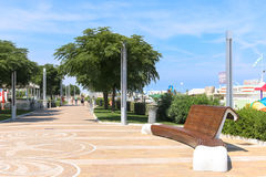 Bench in the pedestrian street Lungomare della Repubblica, Italy. Large curved bench located in a pedestrian street running along the beach Royalty Free Stock Image