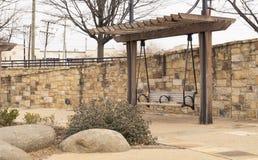Bench pergola in park alongside stone brick wall on gravel walkway. Pergola bench in park alongside stone brick wall on gravel walkway Stock Images