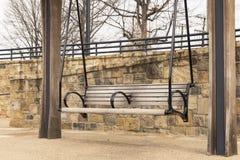 Bench pergola in park alongside stone brick wall on gravel walkway. Pergola bench pergola in park alongside stone brick wall on gravel walkway Royalty Free Stock Photos