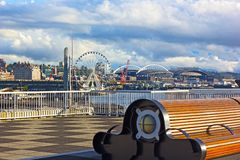 A bench at the Pier 66 with panorama of Puget Sound shore in Seattle, USA. Late afternoon sun touched piers along Alaskan Way in Seattle downtown Royalty Free Stock Image