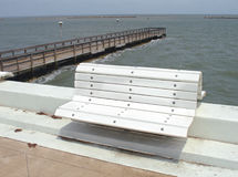 Bench and pier on waterfront. White bench on waterfront with pier and sea in background Royalty Free Stock Photo