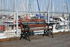 Bench on pier where sea yachts dense parking in calm marina water royalty free stock image